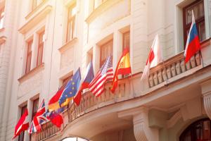 Plusieurs drapeaux de pays différent flottant dans les airs devant un bâtiment
