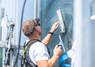 Un professionnel lavant les vitres et châssis extérieurs d'un immeuble