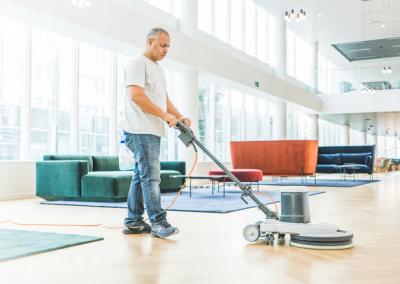 Un technicien de surface nettoyant le hall d'un immeuble avec une autolaveuse