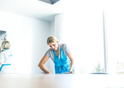 Une femme nettoyant et dépoussiérant des bureaux